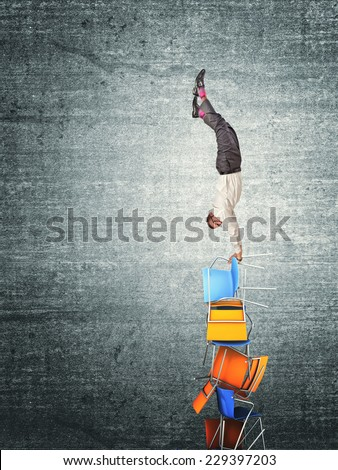 man try acrobat on pile of chairs - stock photo