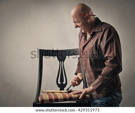 Man trying to fix a chair - stock photo