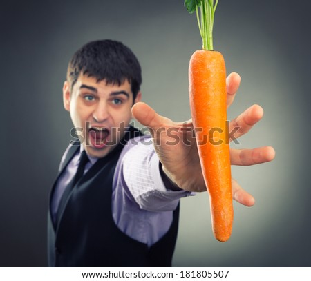 Man trying to reach carrot - stock photo