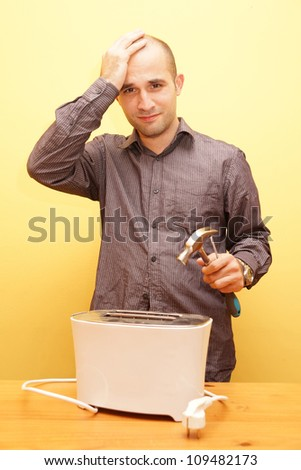 Man trying to repair a broken toaster - stock photo