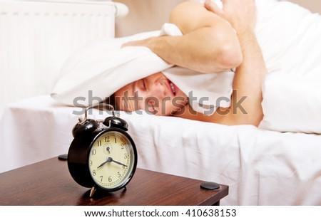 Man trying to sleep, when alarm clock ringing - stock photo