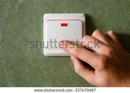 man turning off lights saves energy - stock photo