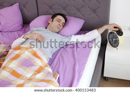 Man turning off the alarm clock, focus on man's face - stock photo