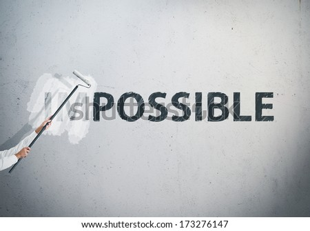 """Man turning the word """"Impossible"""" into """"Possible"""" - stock photo"""