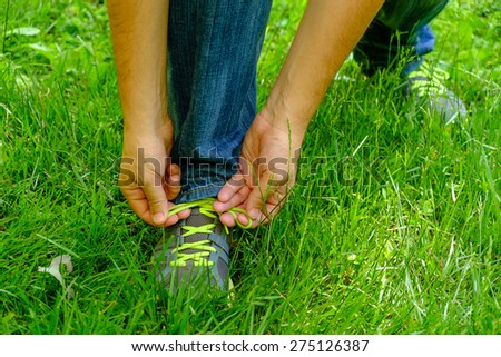 Man tying his shoelaces on his sneakers green grass - stock photo
