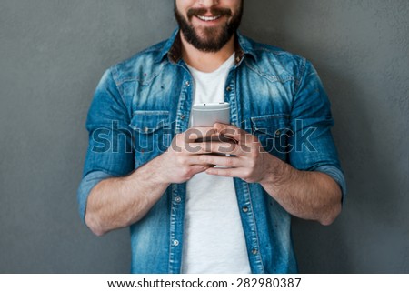 Man typing message. Cropped image of young man holding mobile phone and smiling while standing against grey background - stock photo