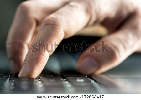 Man typing on a laptop computer inputting data or surfing the internet with a low angle closeup view with shallow dof of his finger depressing a key on the keyboard - stock photo
