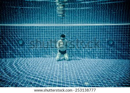 Man underwater in a swimming pool prays - stock photo