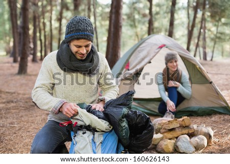 Man unpacking backpack while woman in the tent at the wilderness - stock photo