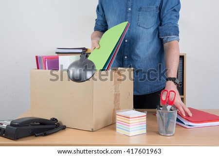 man unrecognizable preparing the box beacause he is fired - stock photo