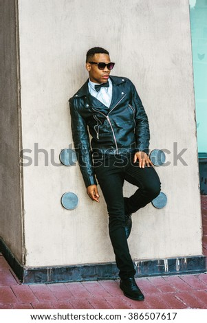Man Urban Autumn/Spring Casual Fashion. Wearing black leather jacket, white undershirt, black bow tie, jeans, sunglasses, African American guy standing against wall on street in New York.  - stock photo