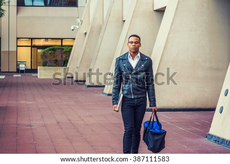 Man Urban Casual Fashion. Wearing black leather jacket, jeans, leather shoes, glasses, holding laptop computer, carrying duffel bag, African American college student walking on street in New York.  - stock photo