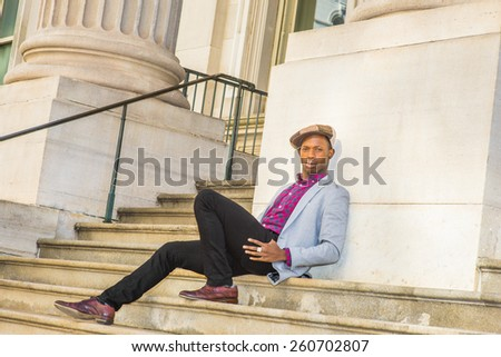 Man Urban Fashion. Wearing newsboy cap, dressing in light gray blazer, patterned pink, black under shirt, black pants, brown leather shoes, a young black guy sitting on stairs, looking at you.  - stock photo