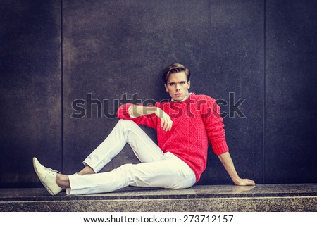 Man Urban Fashion. Young blonde professional, wearing red sweater, white pants, fashion shoes, bending leg, arm resting on knee, sitting on a marble bench, against the wall. Instagram filtered effect. - stock photo