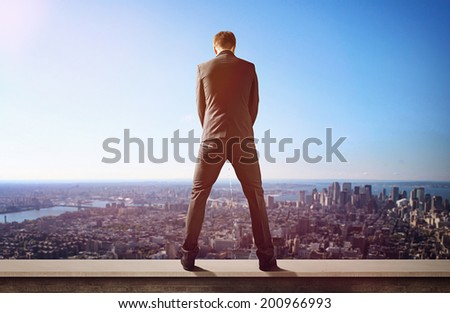 Man urinates from rooftop - stock photo