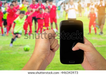 Man use mobile, Motion blur of Kids Playing Soccer Football Match. Sport Soccer Tournament for Youth Teams. Soccer football background. - stock photo