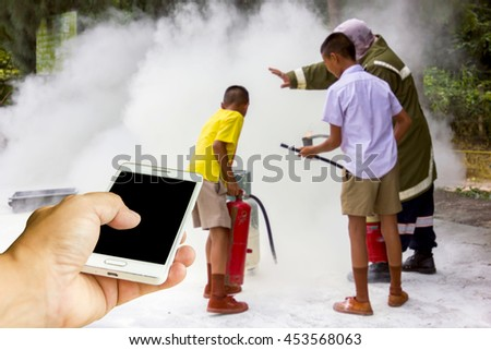Man use mobile phone, Asian boys are trained firefighters as background. - stock photo
