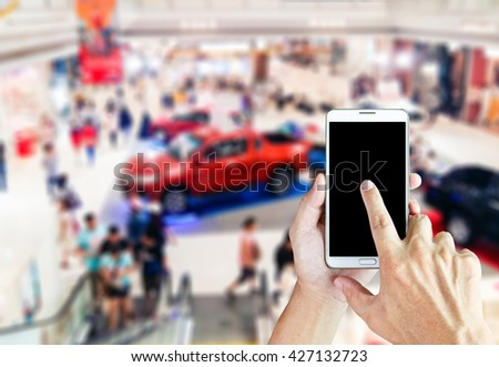 Man use mobile phone, blur image of new car show in the mall as background. - stock photo