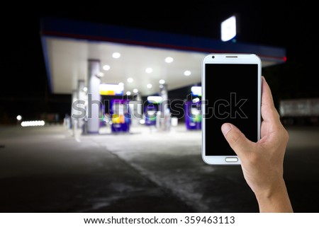 Man use mobile phone , gas station as background. - stock photo