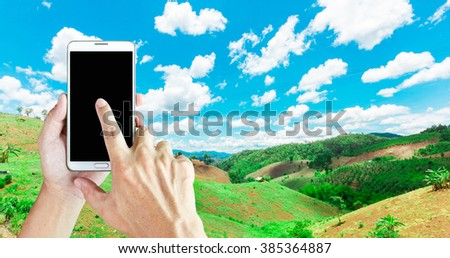Man use mobile phone, image of forest destruction as background. - stock photo