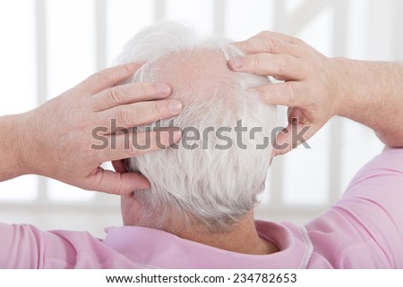 man uses both hands to scratch his head with a beginning of baldness - stock photo