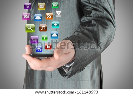 Man uses smart phone with icons on grey background  - stock photo