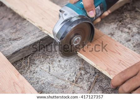 Man using a circular saw to cut plywood - stock photo