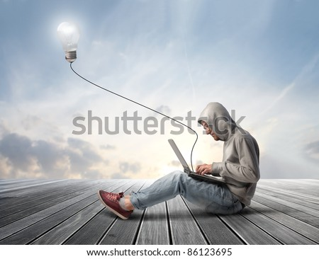 Man using a laptop with light bulb plugged in it - stock photo