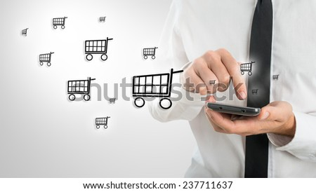 Man using a mobile phone to shop online as he surfs the internet and enters his information and purchase while emitting a clouds of shopping cart icons in a conceptual image. - stock photo