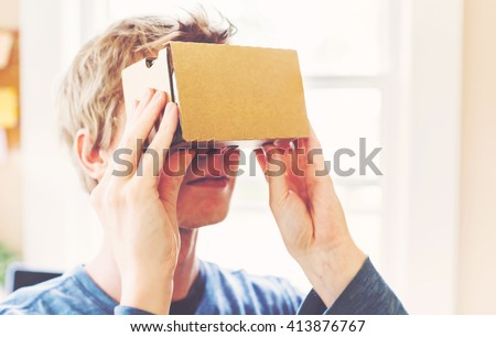 Man using a new virtual reality headset - stock photo