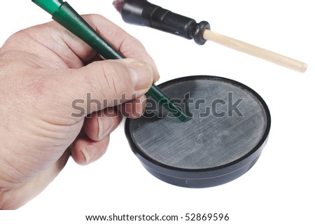 Man using a slate call simulating a hen to attract male turkeys - stock photo