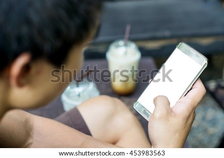 Man using a smartphone in a coffee shop, soft focus. - stock photo