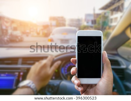 Man using a smartphone while driving a car - Sunset filter effect - stock photo