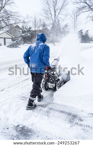 Man Using a Snow Blower to Remove Snow in a Suburban Neighborhood - stock photo