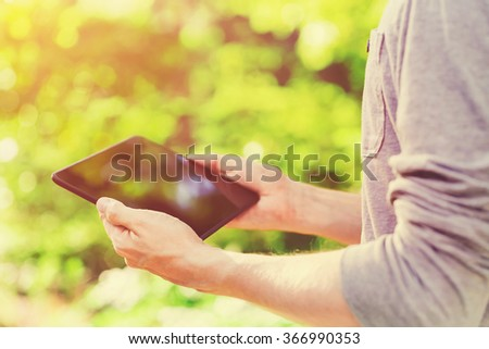 Man using a tablet computer outside in the setting sun - stock photo
