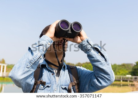 Man using binoculars for birdwatching - stock photo