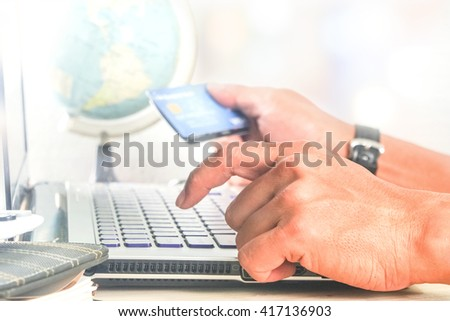 man using computer notebook laptop for shopping online with credit card globe model background selective focus at front hand ,global e-commerce concept - stock photo