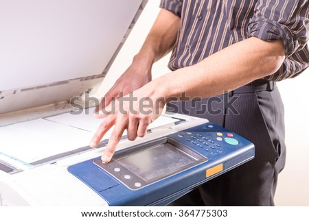 man using copier to make copies of documents - stock photo
