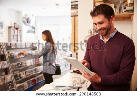 Man using digital tablet behind the counter at a record shop - stock photo