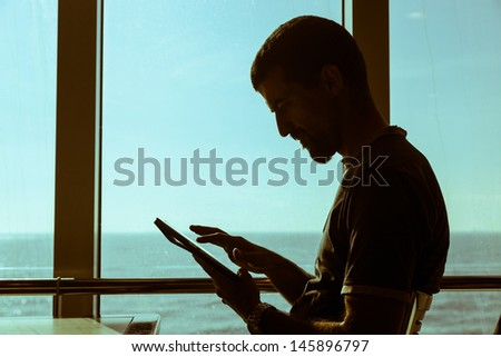 Man Using Digital Tablet on a Ferry Boat - stock photo