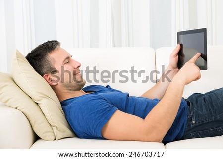 Man Using Digital Tablet While Lying On Sofa At Home - stock photo