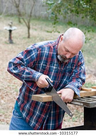 Man using hand saw to cut board - stock photo