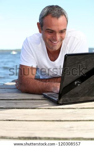 Man using his laptop on jetty - stock photo