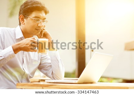 Man using laptop computer while drinking a cup hot milk tea, outdoor cafe, beautiful sunlight during sunset. - stock photo