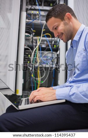 Man using laptop in front of servers in data center - stock photo
