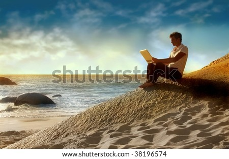 man using laptop on the beach at the sunset - stock photo