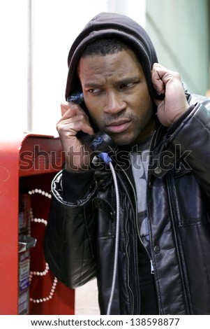 Man using phone booth - stock photo
