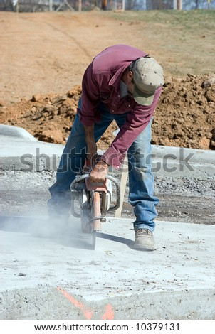 Man using power cutter to cut cement - stock photo