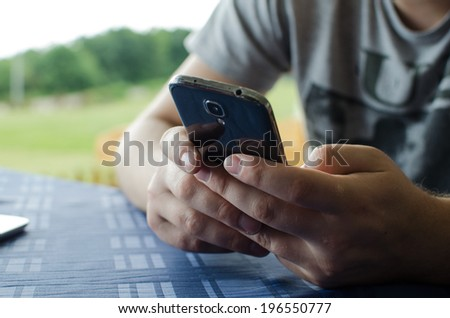 Man using smart phone in nature, Texting - stock photo