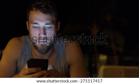 Man using smartphone at night browsing internet updating social media. Young male with beard using mobile cell smart phone outdoors in the dark in summer. - stock photo